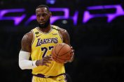nba news-lebron james in yellow lakers jersey holding the ball in one of the nba game