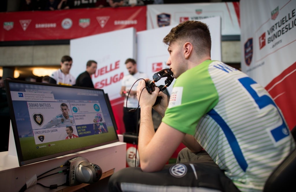 future of the sports industry- a player wearing white and green tshirt holding controller playing fifa game